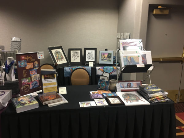 A table with art and books for sale on display.