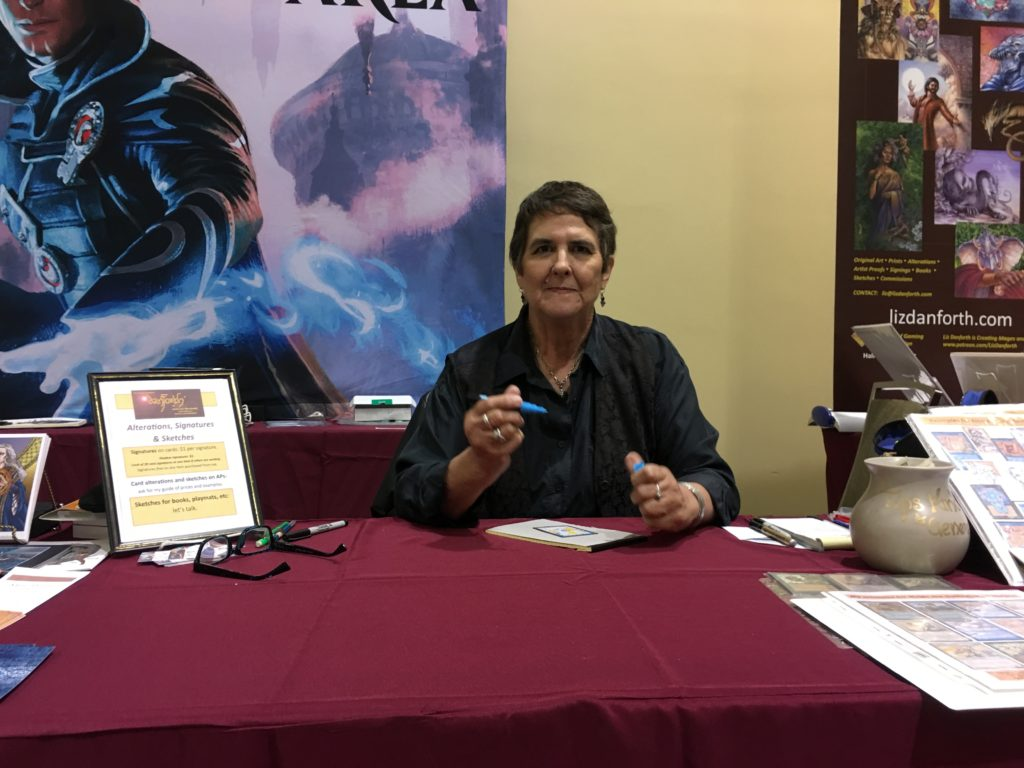 Dark-haired woman Liz Danforth, wearing a black shirt, holding a pen and preparing to sign a card in front of her on the table at a convention.